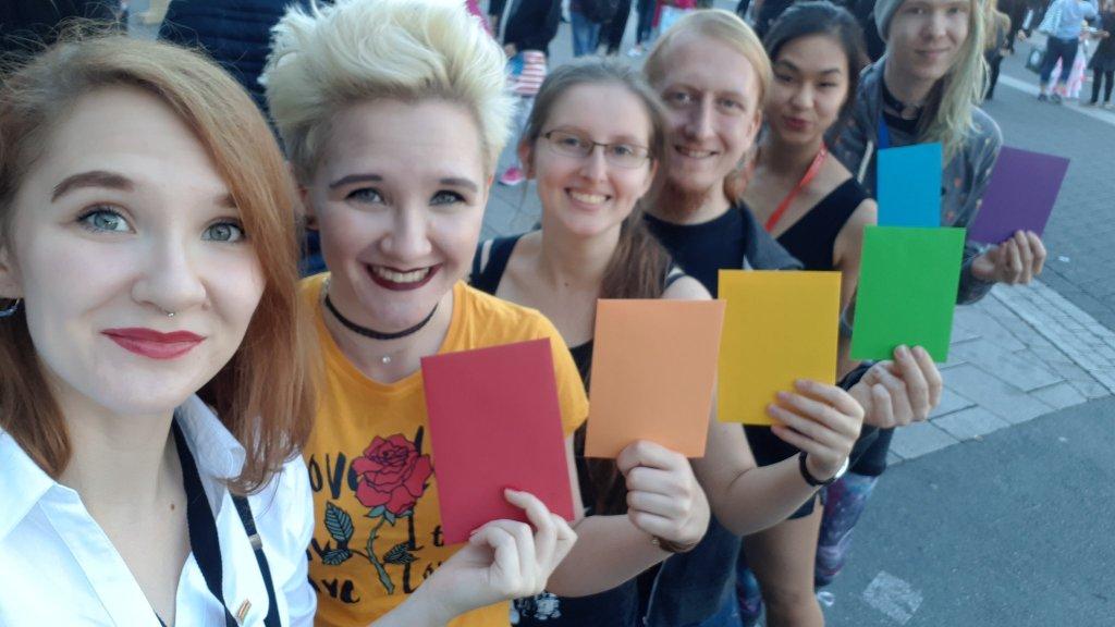 Das Team des Litcamp-BER mit einer weiteren Person; alle tragen regenbogenfarbig angeordnete Karten in den Händen.