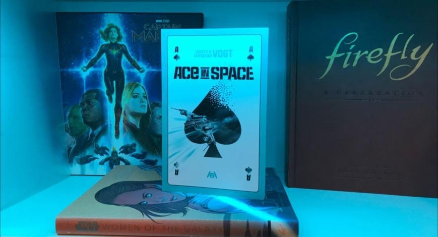 """Buch """"Ace in Space"""" von Judith und Christian Vogt vor einem Bücherregal"""