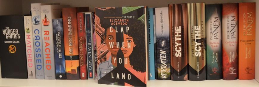 """Buch """"Clap When You Land"""" vor einem Regalbrett in einem gefüllten Bücherregal."""