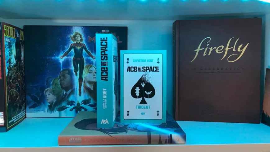 """""""Ace in Space: Trident"""" neben dem Vorgängerband, vor einem Bücherregalbrett"""